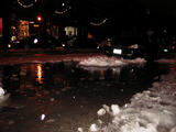 The melting snow makes a river of ninth street...