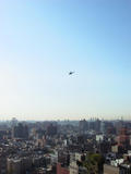A helicopter hovers over the East Village, scoping...